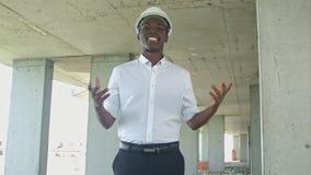 Γελώντας αφρικανικός επιχειρηματίας στη ζώνη κατασκευής που παρουσιάζει κάτι που εξετάζει τη κάμερα Στοκ φωτογραφία με δικαίωμα ελεύθερης χρήσης