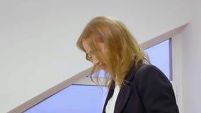 Γελώντας γυναίκα πορτρέτου στο επιχειρησιακό κοστούμι μέσα στο επιχειρησιακό γραφείο κοντά επάνω φιλμ μικρού μήκους