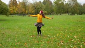 Γελώντας γυναίκα που γυρίζει γύρω από και που χορεύει στα φύλλα φθινοπώρου απόθεμα βίντεο