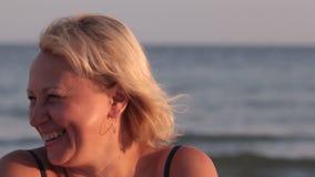 Γελώντας γυναίκα που εξετάζει τη κάμερα και που χαμογελά ενάντια στο σκηνικό των κυμάτων θάλασσας απόθεμα βίντεο