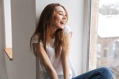 Γελώντας γυναίκα στη συνεδρίαση μπλουζών στο windowsill στοκ φωτογραφία με δικαίωμα ελεύθερης χρήσης