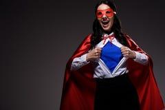 γελώντας ελκυστική έξοχη επιχειρηματίας στο κόκκινο ακρωτήριο και μάσκα που παρουσιάζει μπλε πουκάμισο στοκ εικόνα με δικαίωμα ελεύθερης χρήσης
