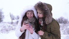 Γελώντας κορίτσια που προσέχουν τις εικόνες στη συσκευή στο υπόβαθρο μειωμένα snowflakes το χειμώνα φιλμ μικρού μήκους