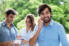 Γελώντας λατινοαμερικάνικος επιχειρηματίας στο τηλέφωνο με τις άλλες επιχειρήσεις Στοκ φωτογραφία με δικαίωμα ελεύθερης χρήσης