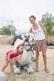 Γελώντας μικρό κορίτσι που αγκαλιάζει τη dromedary συνεδρίαση στην επαρχία και τη μητέρα στοκ εικόνα