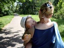 Γελώντας μικρό κορίτσι στους εναγκαλισμούς Mom υπαίθρια στοκ εικόνα