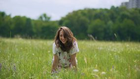 Γελώντας νέα γυναίκα brunette στον πράσινο τομέα χλόης, που στέκεται σε ετοιμότητα γονάτων της φιλμ μικρού μήκους