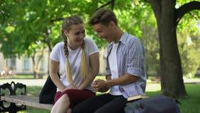 Γελώντας φίλοι που κάθονται στον πάγκο στο πάρκο, που λέει την εξαιρετικά αστεία ιστορία, αστείο απόθεμα βίντεο