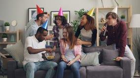Γελώντας φίλοι στο καπέλο κομμάτων που συγχαίρουν το κορίτσι στα γενέθλια που ταΐζει τα πατατάκια της φιλμ μικρού μήκους