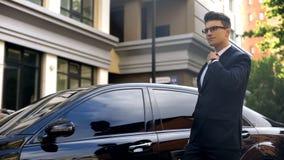 Γεμάτος αυτοπεποίθηση επιχειρηματίας που ισιώνει το δεσμό, που πηγαίνει να εργαστεί, έτοιμο στις προκλήσεις στοκ φωτογραφία