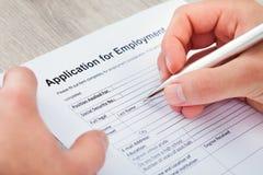 Γεμίζοντας αίτηση χεριών για την απασχόληση Στοκ Φωτογραφίες