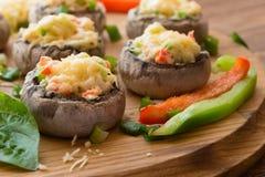 Γεμισμένα μανιτάρια με τα λαχανικά στον ξύλινο πίνακα στοκ εικόνες