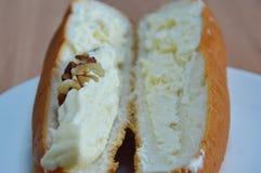 Γεμισμένα ψωμί κρέμα και αμύγδαλο χοτ-ντογκ στο ξύλινο πιάτο πιάτων Στοκ Φωτογραφίες