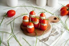 Γεμισμένη ντομάτα με τα ζυμαρικά τυριών κοτόπουλου, σκόρδου και κρέμας που βρίσκονται σε έναν καφετή ξύλινο πίνακα Στοκ Εικόνες