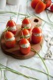 Γεμισμένη ντομάτα με τα ζυμαρικά τυριών κοτόπουλου, σκόρδου και κρέμας που βρίσκονται σε έναν καφετή ξύλινο πίνακα Στοκ φωτογραφία με δικαίωμα ελεύθερης χρήσης