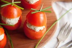 Γεμισμένη ντομάτα με τα ζυμαρικά τυριών κοτόπουλου, σκόρδου και κρέμας που βρίσκονται σε έναν καφετή ξύλινο πίνακα Στοκ Φωτογραφίες