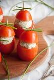 Γεμισμένη ντομάτα με τα ζυμαρικά τυριών κοτόπουλου, σκόρδου και κρέμας που βρίσκονται σε έναν καφετή ξύλινο πίνακα Στοκ εικόνες με δικαίωμα ελεύθερης χρήσης