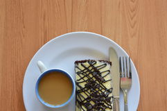 Γεμισμένοι ρόλος κρέμα και καφές μαρμελάδας σοκολάτας με το επιτραπέζιο μαχαίρι στο πιάτο Στοκ Εικόνες