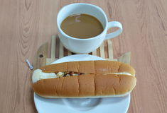 Γεμισμένο κρέμα χοτ-ντογκ ψωμί και αμύγδαλο και καφές στο ξύλινο πιάτο πιάτων Στοκ Εικόνα