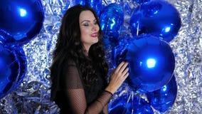 Γενέθλια, κορίτσι με την εορταστική σύνθεση μεταξύ των χρωματισμένων διογκώσιμων μπαλονιών στο υπόβαθρο του λαμπρού τοίχου στο κό απόθεμα βίντεο