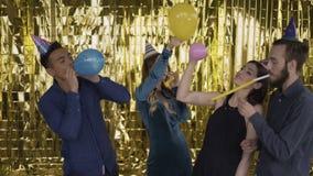Γενέθλια κόμματος Οι τύποι έχουν τη διασκέδαση με τα μπαλόνια 4 άνθρωποι της μικτής φυλής σε ένα χρυσό υπόβαθρο 4K απόθεμα βίντεο