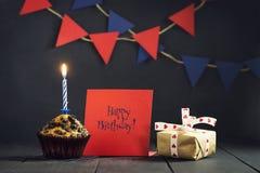 Γενέθλια cupcake σε ένα σκοτεινό υπόβαθρο γενέθλια ευτυχή κάρτα Συγχαρητήρια Στοκ Εικόνες