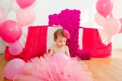 γενέθλια πρώτα Μωρό στη χνουδωτή ρόδινη φούστα, με τα μπαλόνια και ένα βισμούθιο Στοκ Εικόνες