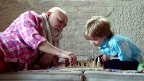Γενεές Σκάκι παιχνιδιού παιδιών Σκάκι παιχνιδιού παππούδων με τον εγγονό του Σκάκι παιχνιδιού παππούδων και εγγονών φιλμ μικρού μήκους