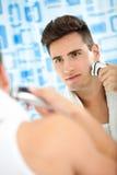 Γενειάδα ξυρίσματος ατόμων με την ηλεκτρική ξυριστική μηχανή Στοκ εικόνα με δικαίωμα ελεύθερης χρήσης