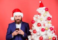 Γενειοφόρα κοστούμι ένδυσης hipster ατόμων επίσημα και smartphone λαβής καπέλων santa Στείλετε τα Χριστούγεννα που χαιρετούν το κ στοκ φωτογραφία