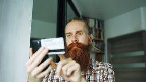 Γενειοφόρες σε απευθείας σύνδεση αγορές ατόμων και κατάθεση με την πιστωτική κάρτα που χρησιμοποιεί το smartphone στο σπίτι Στοκ Εικόνα