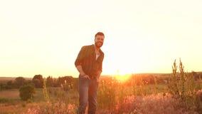 Γενειοφόρες στάσεις ατόμων σε έναν τομέα στο ηλιοβασίλεμα, αργό MO απόθεμα βίντεο