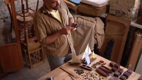 Γενειοφόρες συζητήσεις ξυλουργών στο τηλέφωνο στο εργαστήριό του απόθεμα βίντεο