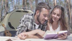 Γενειοφόρος άνδρας πορτρέτου και λατρευτή νέα γυναίκα που βρίσκονται η μια κοντά στην άλλη στη σκηνή στη δασική ανάγνωση το βιβλί φιλμ μικρού μήκους
