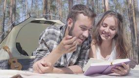 Γενειοφόρος άνδρας πορτρέτου και χαριτωμένη νέα γυναίκα που βρίσκονται η μια κοντά στην άλλη στη σκηνή στη δασική ανάγνωση το βιβ φιλμ μικρού μήκους