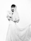 Γενειοφόρος άνδρας σε ένα γαμήλιο φόρεμα γυναικών ` s στο γυμνό σώμα της, που κρατά ένα λουλούδι Στο κεφάλι του ένα στεφάνι των λ Στοκ φωτογραφία με δικαίωμα ελεύθερης χρήσης