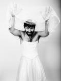 Γενειοφόρος άνδρας στο γαμήλιο φόρεμα μιας γυναίκας στο γυμνό σώμα της, τοποθέτηση αστεία γενειοφόρος νύφη, γραπτή Στοκ Φωτογραφίες