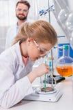 Γενειοφόρος δάσκαλος που εξετάζει λίγο σπουδαστή που κάνει το πείραμα στο εργαστήριο Στοκ φωτογραφία με δικαίωμα ελεύθερης χρήσης