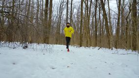 Γενειοφόρος αθλητής στο κίτρινο παλτό που τρέχει προς τη κάμερα στο χιονώδες χειμερινό δάσος απόθεμα βίντεο