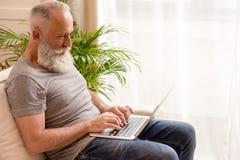 Γενειοφόρος δακτυλογράφηση ατόμων στο lap-top καθμένος στον καναπέ στο σπίτι Στοκ Φωτογραφίες
