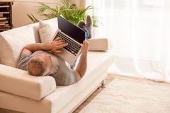 Γενειοφόρος δακτυλογράφηση ατόμων στο lap-top στον καναπέ στο σπίτι Στοκ Εικόνες