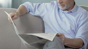 Γενειοφόρος ανώτερη συνεδρίαση ατόμων στον καναπέ και την εφημερίδα ανάγνωσης, ειδήσεις πρωινού Σαββατοκύριακου απόθεμα βίντεο