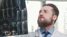 Γενειοφόρος αρσενικός γιατρός που εξετάζει την ανίχνευση mri του ασθενή του απόθεμα βίντεο