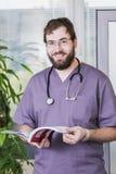 Γενειοφόρος αρσενικός γιατρός στα γυαλιά με ένα βιβλίο διαθέσιμο στο λόμπι Στοκ Εικόνες