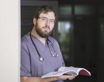 Γενειοφόρος αρσενικός γιατρός στα γυαλιά με ένα βιβλίο διαθέσιμο στο λόμπι Στοκ φωτογραφία με δικαίωμα ελεύθερης χρήσης
