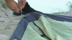 Γενειοφόρος αρσενικός οδοιπόρος που ρίχνει μια σκηνή κοντά στη λίμνη, ταξίδι θερινής στρατοπέδευσης, διακοπές απόθεμα βίντεο