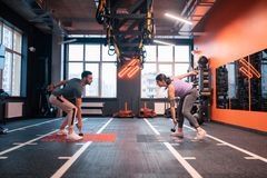 Γενειοφόρος εκπαιδευτής που παρουσιάζει ασκήσεις πελατών του με τα barbells στοκ εικόνα