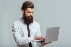 Γενειοφόρος επιχειρηματίας με τη συσκευή Στοκ εικόνες με δικαίωμα ελεύθερης χρήσης
