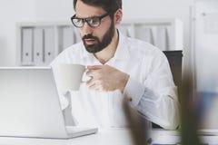 Γενειοφόρος επιχειρηματίας που διαβάζει τα μηνύματα ηλεκτρονικού ταχυδρομείου του Στοκ φωτογραφία με δικαίωμα ελεύθερης χρήσης