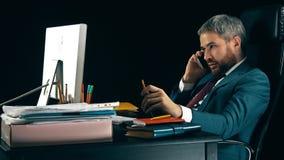 Γενειοφόρος επιχειρηματίας που μιλά στο τηλέφωνο κυττάρων του Υπόβαθρο, που απομονώνεται σκοτεινό Στοκ Εικόνες